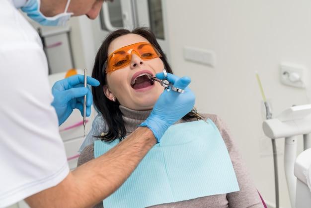 患者に麻酔薬を注射する歯科医