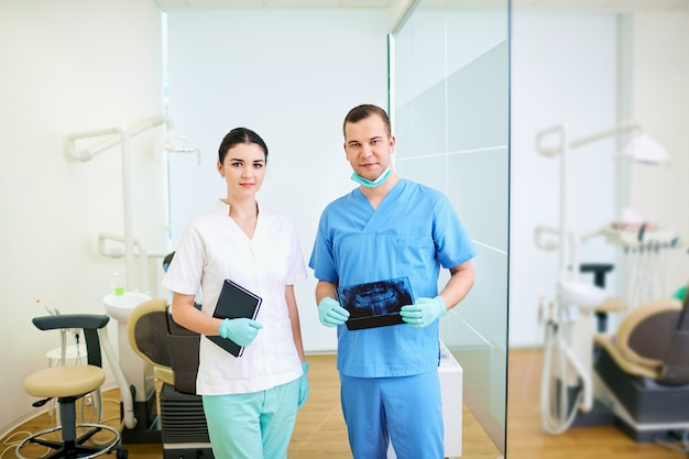 Dentist male and assistant women  the workplace  a dental office