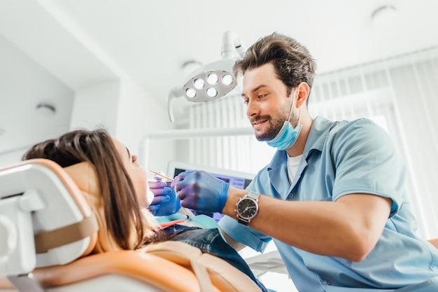 口の歯科掘削機で患者の歯を調べる歯科医の男性。女性の顔のクローズアップビュー
