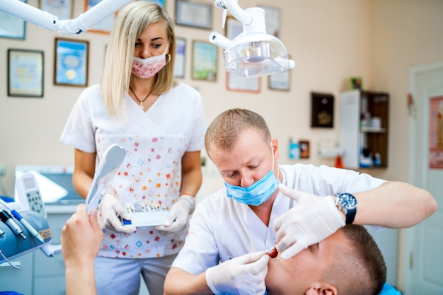 Dentist man doing a dental treatment on a young man patient. young womam assistant.