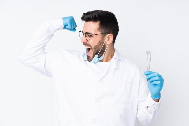 勝利を祝っている白い壁に分離されたツールを保持している歯科医の男