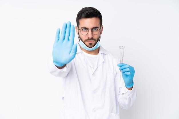 彼女の手で停止ジェスチャーを作る白い壁に分離されたツールを保持している歯科医の男 Premium写真
