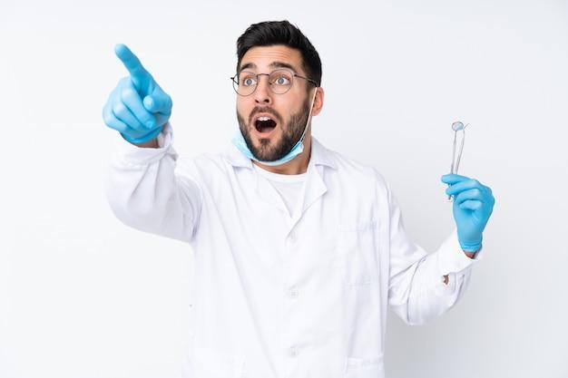 離れて指している白い壁に分離されたツールを保持している歯科医の男