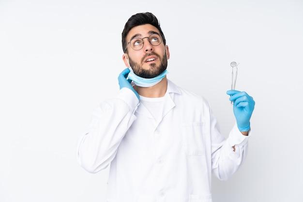 Человек дантиста держа инструменты изолированные на белой стене думая идея