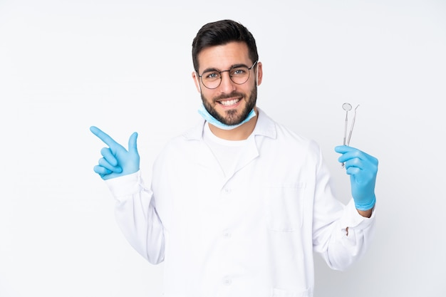 Dentist man holding tools isolated on white wall pointing finger to the side