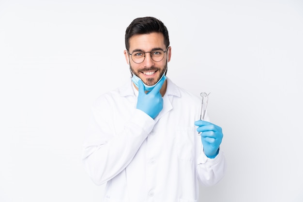 Dentist man holding tools on white laughing