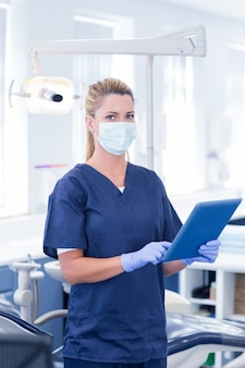Dentist in mask using her tablet and looking at camera at the dental clinic