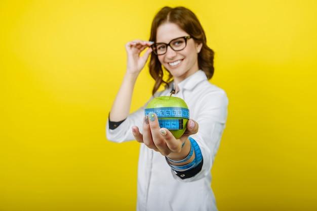 Женщина врача дантиста держит зеленое свежее яблоко в руке и зубной щетке. врачи-стоматологи. женщины-врачи.