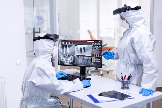 Dentist and nurse discussing patient teeth issues dressed in ppe suit. medical specialist wearing protective gear against coronavirus during global outbreak looking at radiography in dental office.
