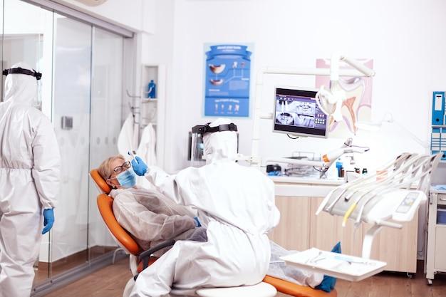 デジタル体温計を使用して化学防護服を着て患者の体温を測定する歯科医の看護師。歯科医院での診察中に防護服を着た年配の女性。