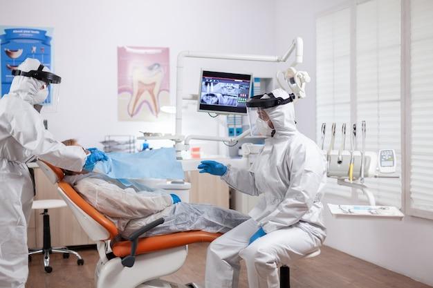 デジタル体温計を使用して化学防護服を着用して患者の体温を測定する歯科医の看護師
