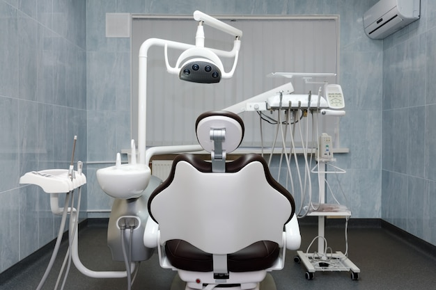 Dentist office. modern dental cabinet. dental instruments and tools in modern clinic, professional dentistry chair waiting to be used by orthodontist