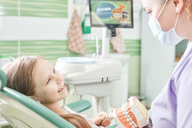 Дантист в защитной маске и ребенок с экраном в стоматологическом кабинете. молодая девушка с первым визитом к стоматологу