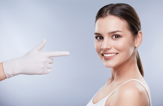 Dentist and patient, teethcare. healthcare, stomatological concept for dentists. hand in white glove pointing at smiling beautiful girl with snow-white teeth