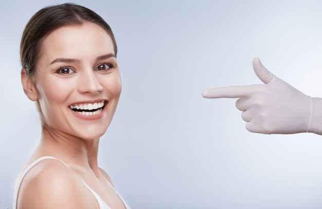 Dentist and patient, teethcare. healthcare, stomatological concept for dentists. hand in white glove pointing at smiling woman with snow-white teeth
