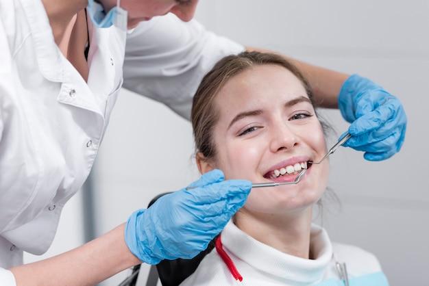 Стоматолог выполняет стоматологическое обследование пациента