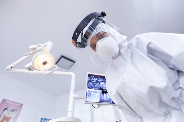 치과 진료실에서 치료하는 동안 covid 발병에 대한 보호 장비를 착용하는 치과 의사의 관점. 환자의 건강을 확인하는 동안 코로나바이러스에 대한 안전 장비를 착용하는 stomatolog.