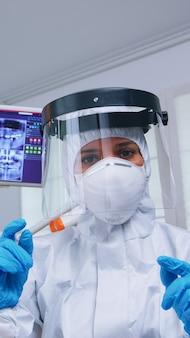 歯科医院での治療を説明するcovidの発生に対する保護具を身に着けている歯科医の視点。患者のヘルスケアチェック中にコロナウイルスに対する安全装備を身に着けているstomatolog。