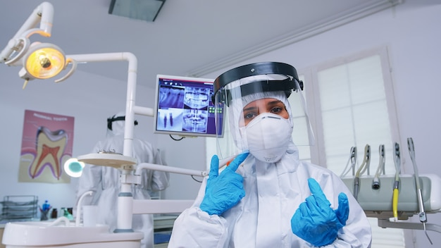 Dentist point of view wearing protection gear against covid outbreak explaining treatment in dental office. stomatolog wearing safety gear against coronavirus during heatlhcare check of patient.