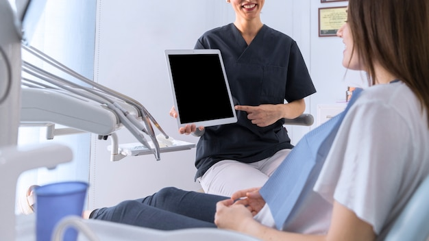 Dentist pointing on digital tablet screen to female patient sitting on chair