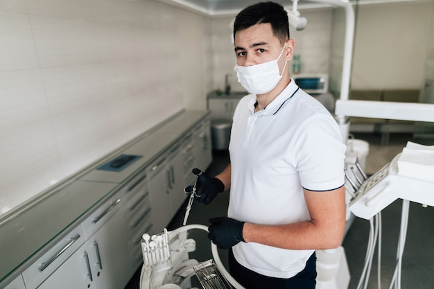 Dentist posing with surgical equipment and mask