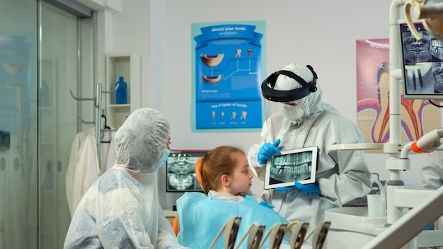 Dentist in protective equipment showing on tablet dental x-ray reviewing it with mother of kid patient. medical team wearing face shield coverall, mask, gloves, explaining radiography using notebook