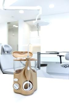 Золотой спринклерный ирригатор стоматолога стоит на столе на ярко-белом фоне