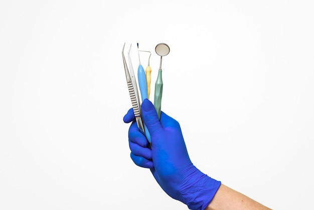 The dentist's hand in a blue glove holds dental instruments.