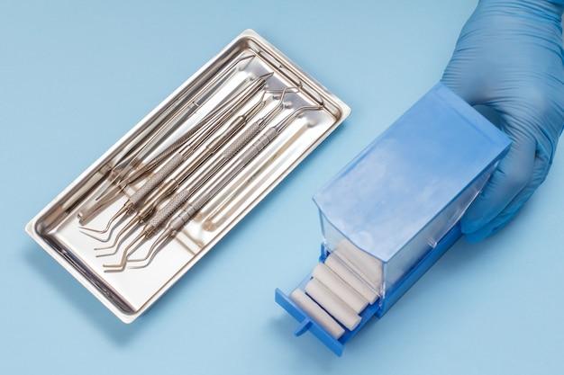 면 탐폰 플라스틱 상자가 있는 라텍스 장갑을 끼고 있는 치과 의사의 손, 강철 트레이에 치과 치료를 위한 복합 충전 도구 세트. 의료 도구 개념입니다. 평면도.