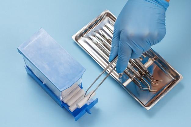 핀셋이 달린 라텍스 장갑을 끼고 있는 치과 의사의 손이 면 탐폰을 들고 있습니다. 배경에 있는 강철 트레이에 치과 치료를 위한 복합 충전 도구 세트. 의료 도구 개념입니다. 평면도.