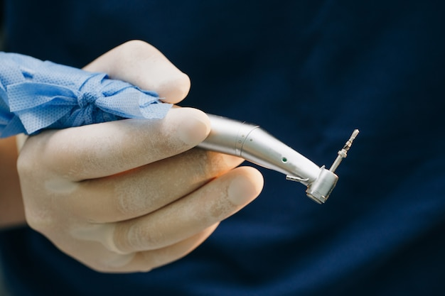 Dentist's hands with gloves working with dental drill in dental office