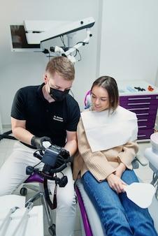 Стоматолог показывает внутриротовую фотографию зубов пациентке, сидящей в стоматологическом кресле.