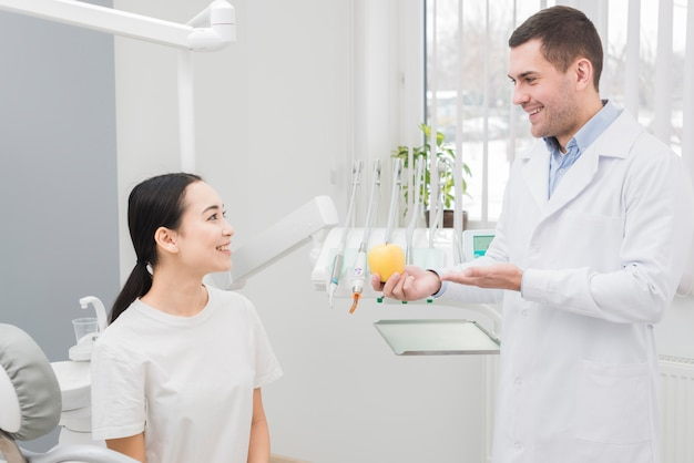 Dentist showing apple to patient