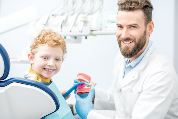 Dentist showing the boy how to brush teeth on artificial jaw at the dental office