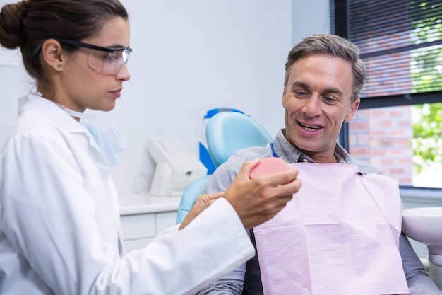 Dentist showing dental mold to man