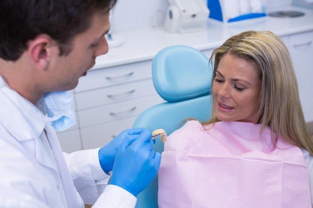 Dentist showing dentures to patient
