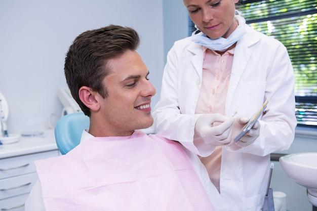 Стоматолог показывает цифровой планшет пациенту
