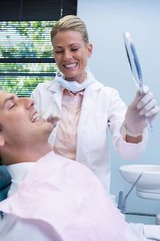 Dentist showing mirrior to patient