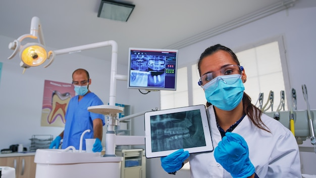患者と一緒にそれをレビューしている錠剤の歯のx線写真に表示されている歯科医。現代の口腔病クリニックで一緒に働いている医師と看護師が、ノートブックディスプレイを使用して歯の老婆x線撮影を説明します