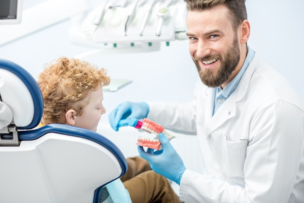 치과 사무실에서 인공 턱에 양치질 하는 방법을 소년을 보여주는 치과 의사