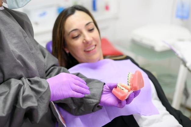 치과 의사는 환자에게 치과 교정 치과 모델을 보여 주며 환자에게 치과 클리닉에서 교정 치료를 설명합니다. 고품질 사진