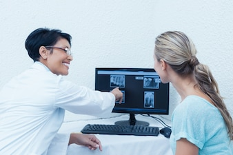 Dentist showing woman her mouth x-ray on computer