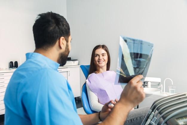 Стоматолог показывает рентген во время стоматологического лечения