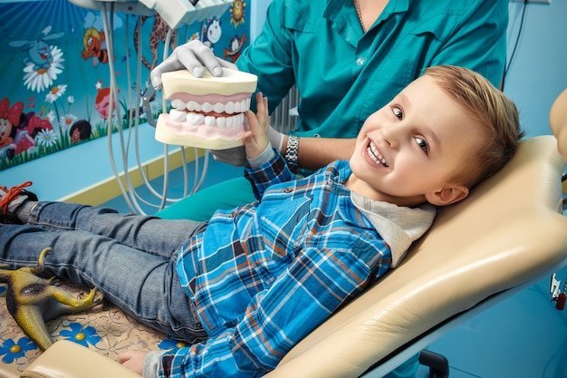 Dentist shows a denture to the little boy
