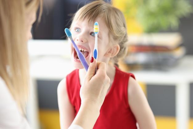 Стоматолог показывает маленькой девочке зубные щетки и правильные движения для ухода за полостью рта