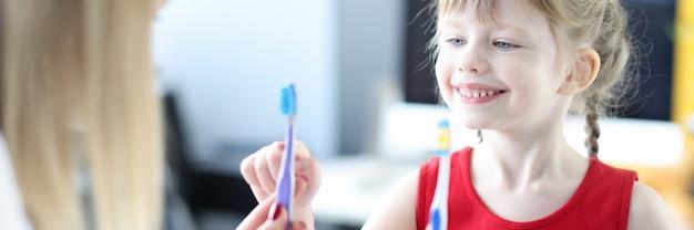 歯科医は小さな女の子に2本の歯ブラシのクローズアップを示しています