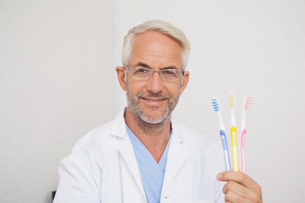 Dentist smiling at camera holding toothbrushes