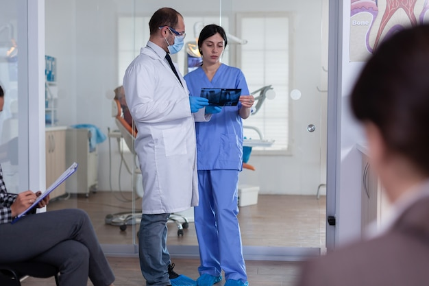 Dentist in stomatology waiting area holding patient x-ray explaining diagnosis to nurse in a crowded hallway with patient filling form. dentistiry staff in reception.