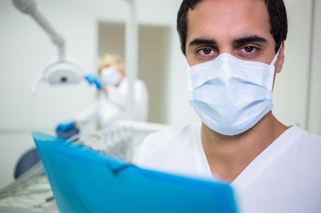 Dentist in surgical mask in dental clinic