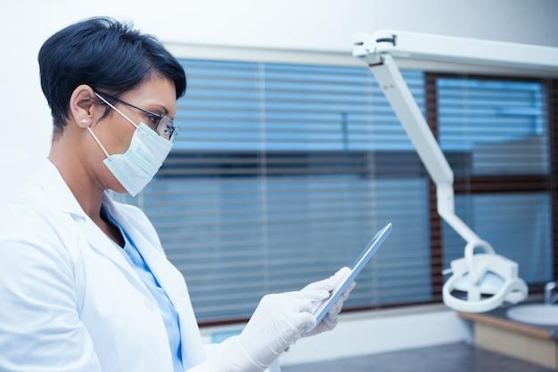 Dentist in surgical mask using digital tablet
